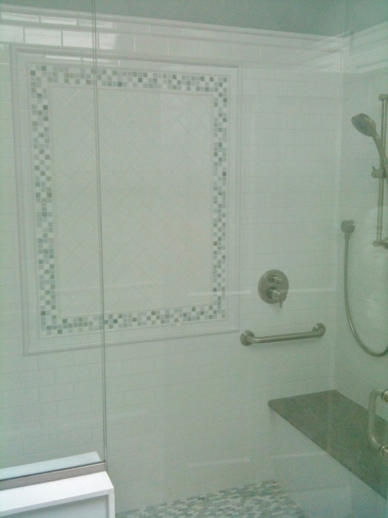 7 Foot stall shower with marble bench, and multiple shower heads.